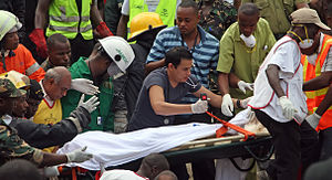 2013 Dar es Salaam building collapse - Members of the Tanzanian Red Cross excavate a victim from the rubble