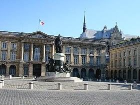 Monument à Louis XV au milieu de la place, devant la sous-préfecture, et la cathédrale à l'arrière-plan.