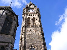 The view up a huge clock tower from the ground upwards. The ornate, angular tower is made of stone and appears a light-taupe colour. It fills the middle part of the image. The top of the tower has a large beige clockface, and above that, a stone spire. In the background is the sky which appears mostly as vivid azure but partly with white clouds.