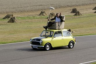 "Mr. Bean - Rowan Atkinson demonstrating a famous scene from the episode ""Do-It-Yourself Mr. Bean"" on a Mini at Goodwood Circuit"
