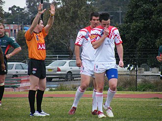 "Rugby league match officials - A referee sends a player to the ""sin bin"" for ten minutes. Spread fingers are used as the signal instead of a yellow card."