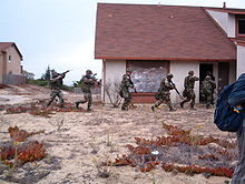 Group of soldiers enter into an abandoned residential building.
