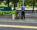 Security guard writing up a bicycle for weekend parking. (14257217025).jpg