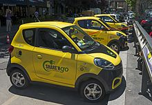 "A line of small two-door yellow cars parked diagonally against a curb. Several have curled red charging cords connecting them with a charging station on the curb. On the side of the one nearest the camera is written the words ""Share N' Go: the new mobility"" with a stylized electric cord curling around the words on their left"