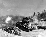 "A Sherman tank fires its 76 mm gun at enemy bunkers on ""Napalm Ridge,"" in support of the 8th ROK Division May 11, 1952."