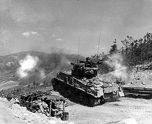 "Tanks of South Korea - Supporting the 8th ROK Army Division, a M4A3E8 Sherman tank fires its 76mm gun at KPA bunkers at ""Napalm Ridge"", Korea, 11 May 1952"