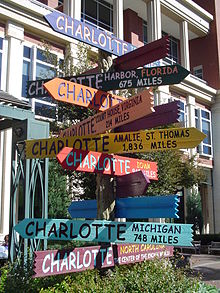 """Schilderbaum in Charlotte, North Carolina, der die Entfernung zu anderen Städten namens """"Charlotte"""" anzeigt. (Quelle: Wikimedia)"""