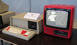 A computer in a red case with a separate monitor and keyboard. The monitor is displaying a vector graphic of a wave.
