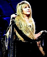 Stevie Nicks is pictured on stage holding a microphone and looking to her left