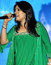 Sunidhi Chauhan performing on stage wearing a green dress