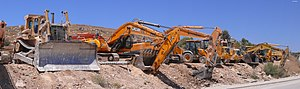 Heavy equipment - Caterpillar D9L bulldozer, excavators and other heavy equipment vehicles parked near a quarry in Israel