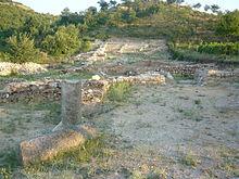 Photographie en couleur de ruines, des fondations de maison, en bord de colline