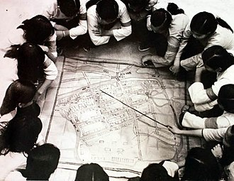 Tet Offensive - Special forces of the People's Liberation Armed Forces of South Vietnam study maps of District 7, Saigon, prior to the Tet Offensive