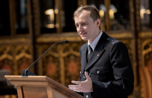 Tom Scholes-Fogg speaking at the 999 Festival of Thanksgiving in 2018.png
