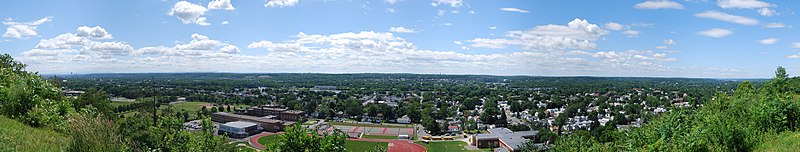 A wide panoramic shot begins and ends in bushes but is graced by two and three story city houses throughout most of the image. Front and center are three large schools featuring a track, tennis courts, and a football field. Behind the houses is a river flowing right to left.