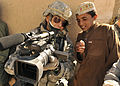 U.S. Air Force Master Sgt. Robert Carreon, with the 4th Combat Camera Squadron, shows his video recording to a student at the Wazi Muhammad Khan School in Hutal, Afghanistan, Jan. 7, 2010 100107-F-PU334-121.jpg