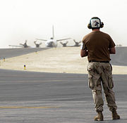 US Navy 050925-F-0375W-006 U.S. Navy Aviation Structural Mechanic 1st Class Greg Eriksen, assigned to Commander Task Group 57.1, waits for an EP-3E Aries aircraft to taxi after a flight from Bahrain