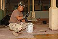 US Navy 051229-N-4374S-007 Construction Electrician 1st Class Reynaldo Pacleb, a U.S. Navy Seabee assigned to Naval Mobile Construction Battalion Three (NMCB-3), installs ceramic floor tile during floor restoration.jpg