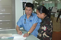 US Navy 060526-N-9076B-039 Project Hope volunteer Joel Trinadad, left, and Captain Annieve Adversario of the Armed forces Philippines Nurse Corp