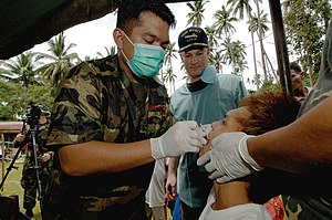 Dentistry in the Philippines - In Isabela, Basilan, at the Zamboanga Peninsula, Philippines on May 29, 2006: A tooth extraction technique being employed by Filipino military male dentist to a patient was being observed by US Col. and USNS Mercy Dental Officer Jeffery Swartz of Smithtown, New Jersey, USA.