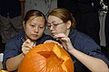 US Navy 071021-N-0913B-022 Aviation Ordnance Specialist Airman Darlene Vue, and Aviation Support Equipment Technician Airman Chelsea Thompson carve a pumpkin during a Morale, Welfare and Recreation (MWR)-sponsored event.jpg
