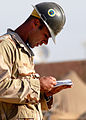 US Navy 071130-N-0553R-002 Equipment Operator 1st Class Jason Knifley, assigned to NMCB-1, consults the Navy's crane manual prior to commencing a maximum load crane certification at Camp Ramadi.jpg