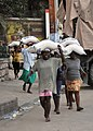 US Navy 100131-N-6214F-019 Women carry 55-pound bags of rice distributed by the World Health Organization at a food distribution site in Port-au-Prince, Haiti.jpg