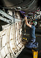 US Navy 111012-N-BT887-217 Aviation Electrician's Mate Airman Michael Sawyer performs maintenance on the engine of an F-A-18C Hornet.jpg
