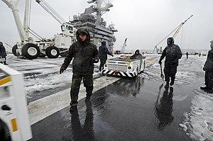 US Navy 120120-N-HN953-014 Sailors aboard the aircraft carrier USS Nimitz (CVN 68) remove snow from the ship's flight deck.jpg