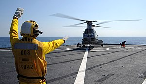 US Navy 120201-N-LP801-567 Boatswain's Mate 2nd Class Caesar Castro directs a CH-46 Sea Knight helicopter during flight operations aboard the forwa.jpg