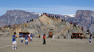 Uummannaq - Football match in Uummannaq. Salliaruseq Island in the background