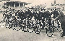 A lineup of men on bicycles