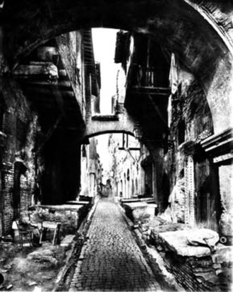 """Sant'Angelo, Rome - The old fish market (""""La Pescheria"""") in via del Portico d'Ottavia (ca.1860). The marble slabs where the fish was sold are visible on both sides of the road. The houses on the left were demolished together with the Ghetto in 1885, while those on the right are still in place, and host some of the best Jewish restaurants in the Ghetto."""