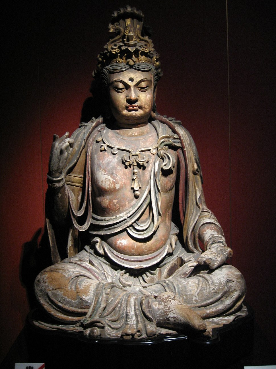 A wooden carving of a slightly overweight Buddha, sitting in a cross legged position. Clothing, including a shirt that covers the shoulders but leaves the chest exposed, and long, baggy pants, are carved into the statue.