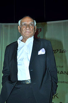 Yash Chopra is standing with his hands in his pockets, and looking away from the camera
