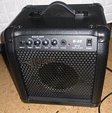"A small, lightweight practice amplifier/speaker cabinet is shown. Like most ""combo"" amplifiers, it has a built-in carrying handle."