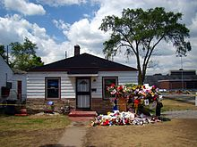 The single-storey house has white walls, two windows, a central white door with a black door frame, and a black roof. In front of the house there is a walk way and multiple colored flowers and memorabilia.