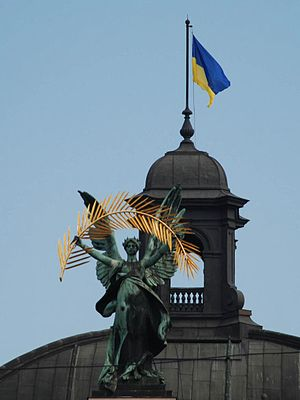 Flag of Ukraine - Flag flying on Lviv Theatre of Opera and Ballet with statue of Glory