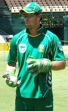 A man wearing a green top and cap, light green gloves and black goggles