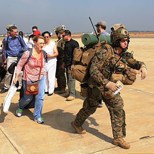 A U.S. Marine, right, assigned to Special Purpose Marine Air-Ground Task Force Crisis Response, guides U.S. citizens down a flight line in Juba, South Sudan, during an evacuation of personnel from the U.S 140103-M-HF911-006.jpg