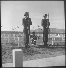 A little Korean girl places a wreath of flowers on the grave of an American soldier, while Private First Class... - NARA - 530634