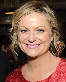 Amy Poehler smiles broadly at the camera.