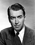 Black and white photo of James Stewart in 1948—an elegant white man with arched eyebrows and short, smooth hair combed to the side, around 40 years old.