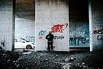 Artist XVALA with Pepe meme mask under the bridge at the Calais Jungle, Calais, France 2019.jpg