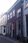 foto van Meester Geertshuis. Onderkelderd huis met lijstgevel op plint. Op de verdieping vensters met geprofileerde natuurstenen dorpels. Kelderlicht met traliewerk