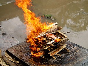 Funeral - A Hindu cremation rite in Nepal. The samskara above shows the body wrapped in saffron red on a pyre.