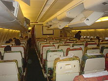 The interior of a DC-10 aircraft showing the backs of seats. The overhead lockers are mostly open.