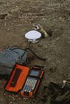 Black footed ferret at borrow entrance investigating scientific equipment.jpg