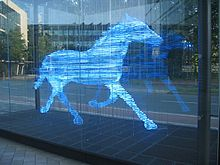 Photograph of a sculpture of a trotting horse. The sculpture was made using a series of horizontal bands. Each band is made from a glass tube that glows blue. The bands are stacked to indicate the form of a horse; the separation between the bands has about the same width as the glass tubing. The sculpture is inside a large glass box that has been placed on the plaza between some office buildings.