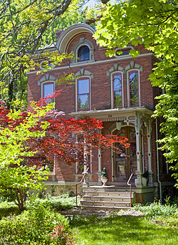 A brick house with ornate arches above its windows seen from slightly to its left though red and green leaves catching the sunlight